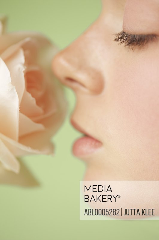 Extreme close up of a young woman profile inhaling a pink rose