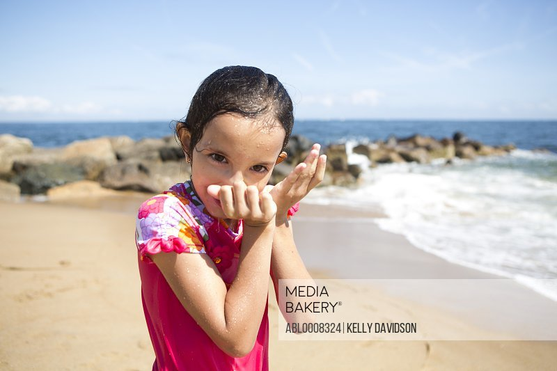 Girl on Beach Wiping Water off Face