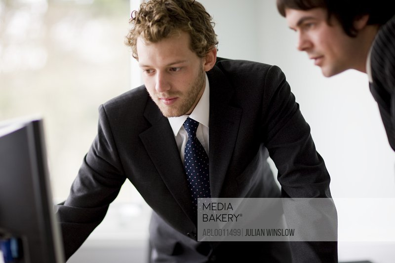 Close up of two young businessmen looking at computer monitor