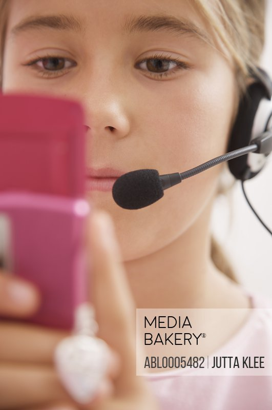 Close up of a girl wearing a headset and holding a mobile phone