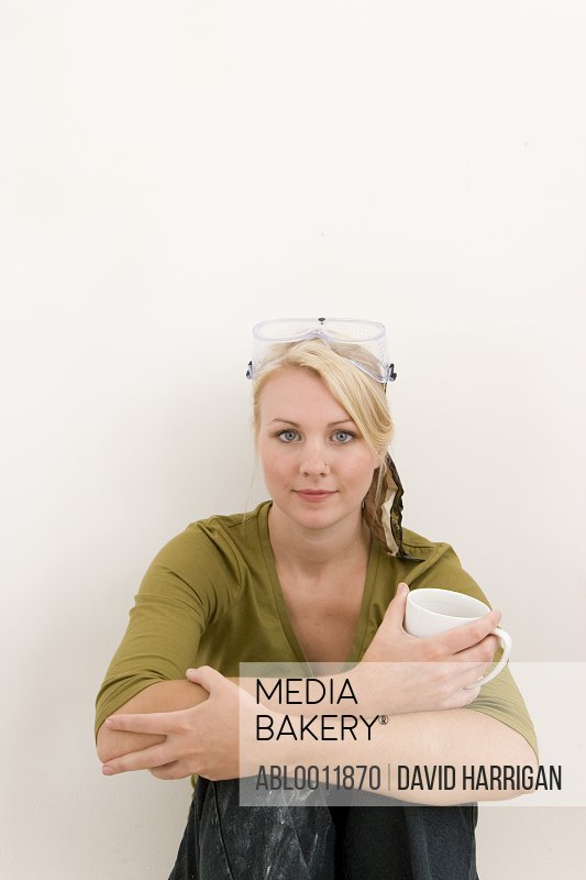Woman sitting against white wall with arms around knees holding a coffee cup
