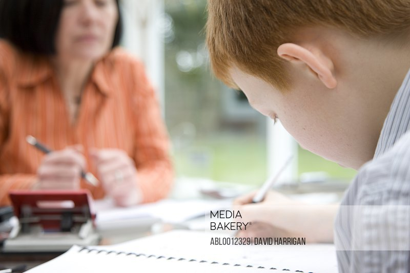 Close up of a boy doing homework with  woman supervising