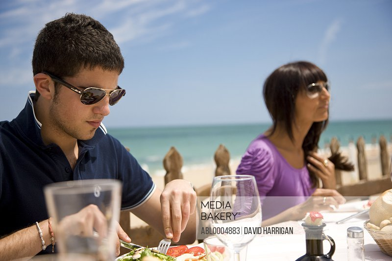 Young man and woman having lunch al fresco by the sea