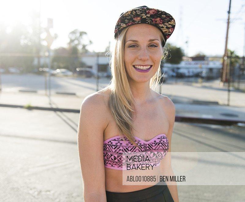 Smiling Young Woman Wearing Baseball Cap on Street