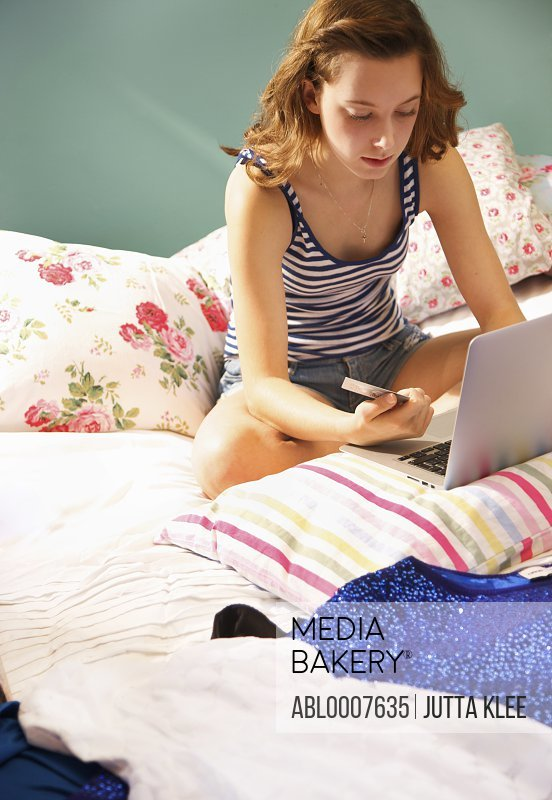 Teenage Girl Sitting on Bed Shopping Online with Credit Card
