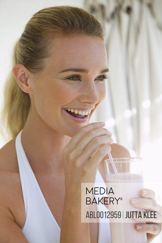 Woman drinking a yogurt smoothie with a straw