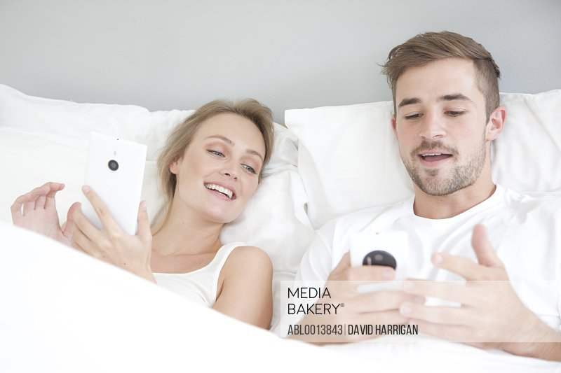 Couple in Bed Using Smartphone