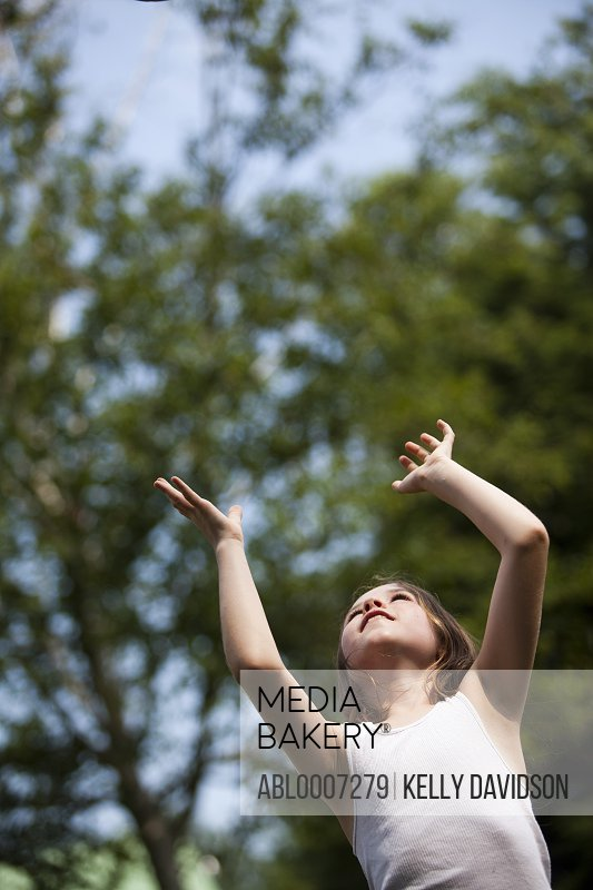 Young Girl with Arms Raised Looking Up