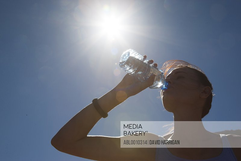 Woman Drinking Water from Bottle against Blue Sky