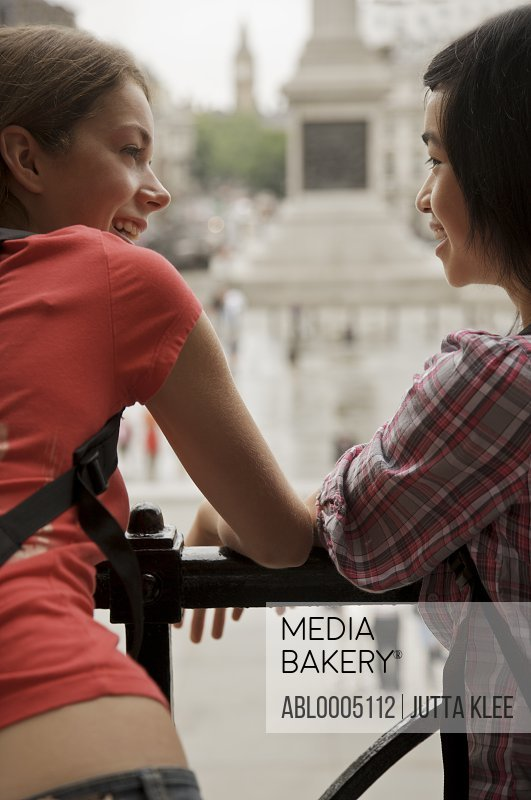Two smiling teenaged girls leaning over a balustrade in London Trafalgar Square