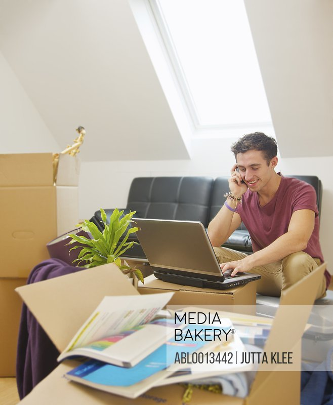Man Sitting amongst Boxes Using Laptop and Cell Phone