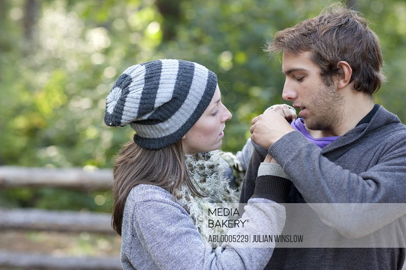 Young woman checking man shoulder