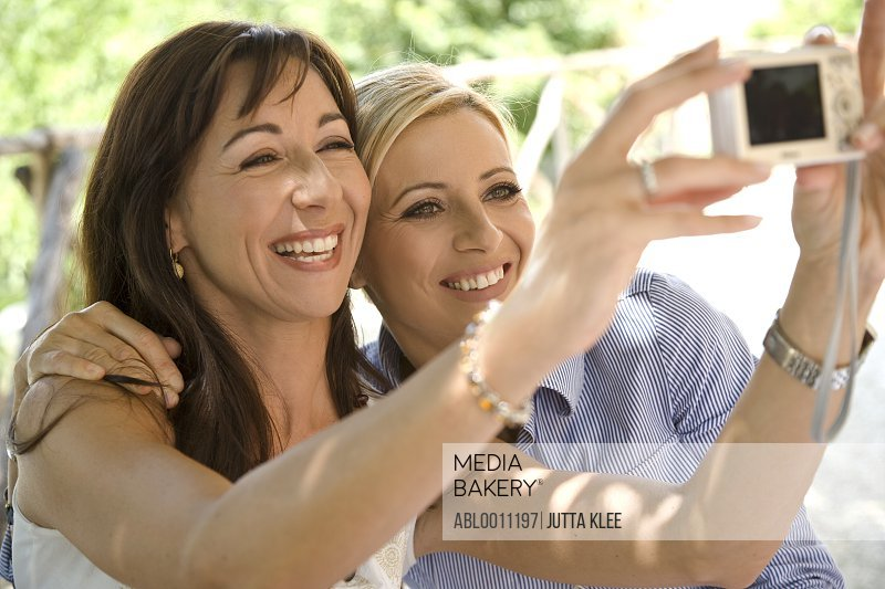 Two women holding digital camera and taking self-portrait
