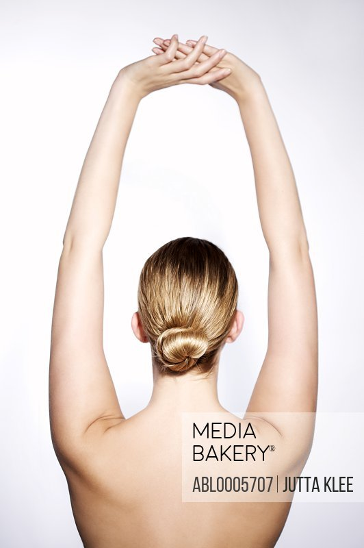 Back view of a young woman with her arms stretched above her head