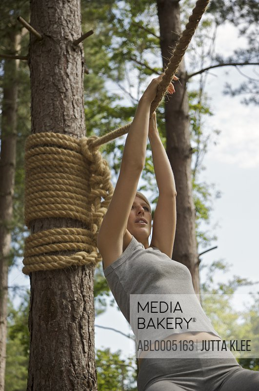 Young woman at obstacle course hanging from a rope