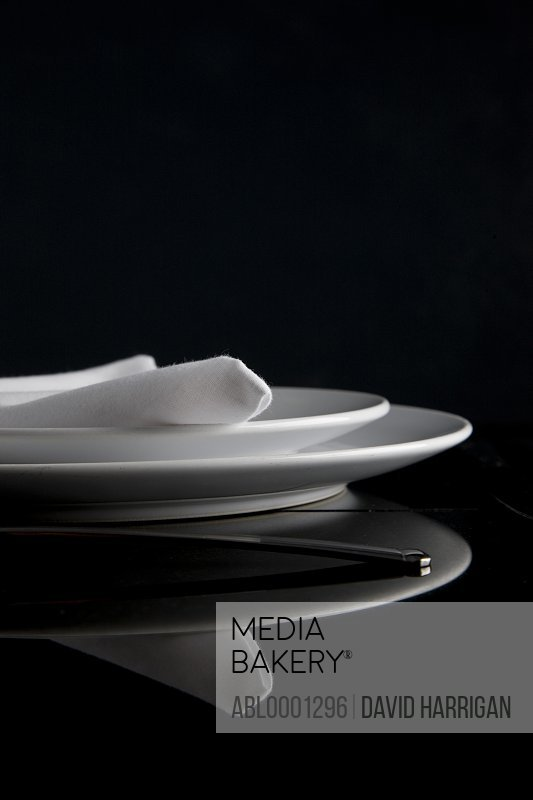 Close up of a place setting with plates and napkin on a glass table