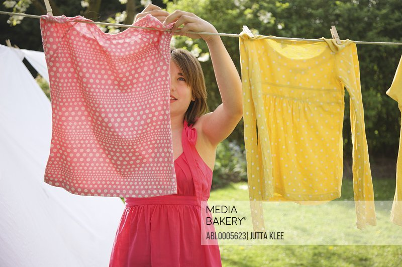Teenaged girl hanging t-shirts on a clothesline
