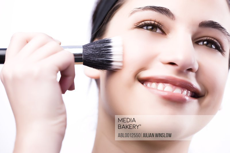 Close up of a smiling woman applying make with a blush brush