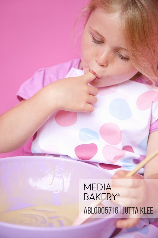 Young girl holding a baking bowl sucking her finger