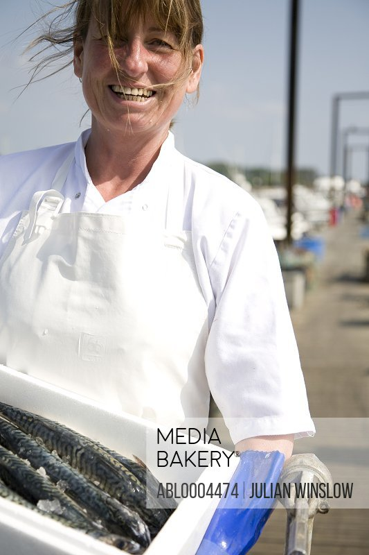 Portrait of smiling fishmonger holding a white container full of fish