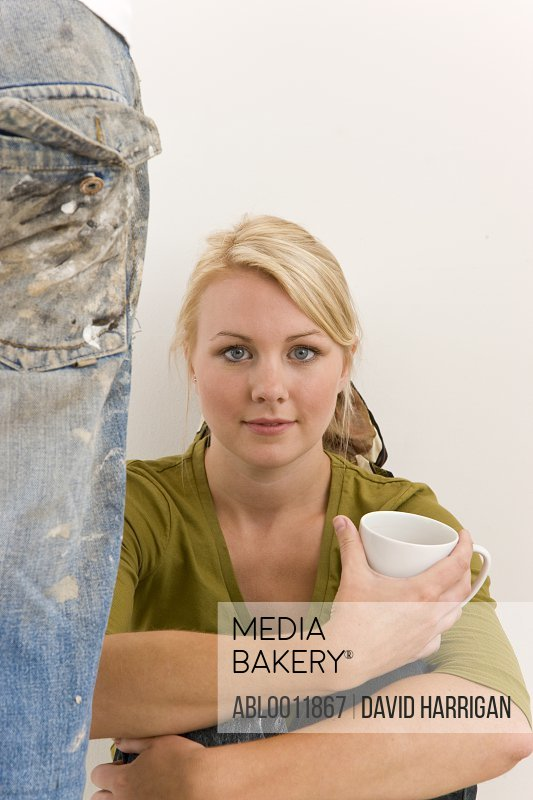 Woman sitting against white wall holding a coffee cup