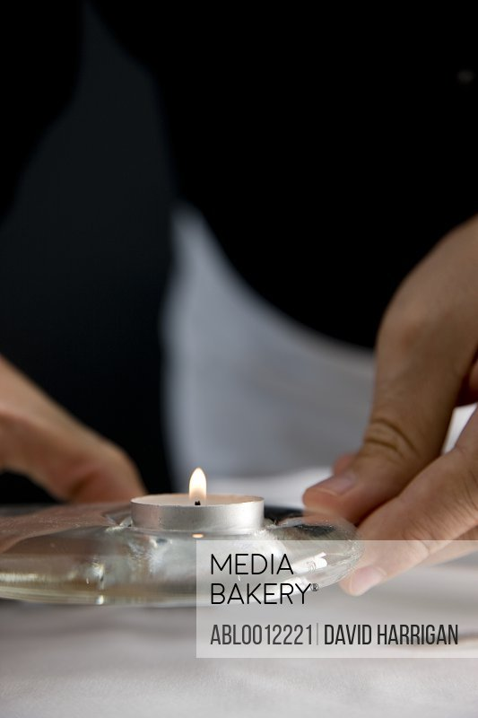 Close up of a waiter hands positioning a tea light on a restaurant table