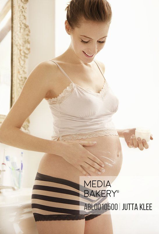 Pregnant Woman Applying Beauty Cream on her Stomach