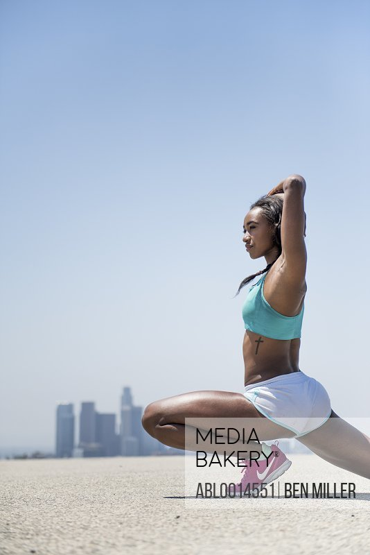 Woman Stretching, Cityscape in background