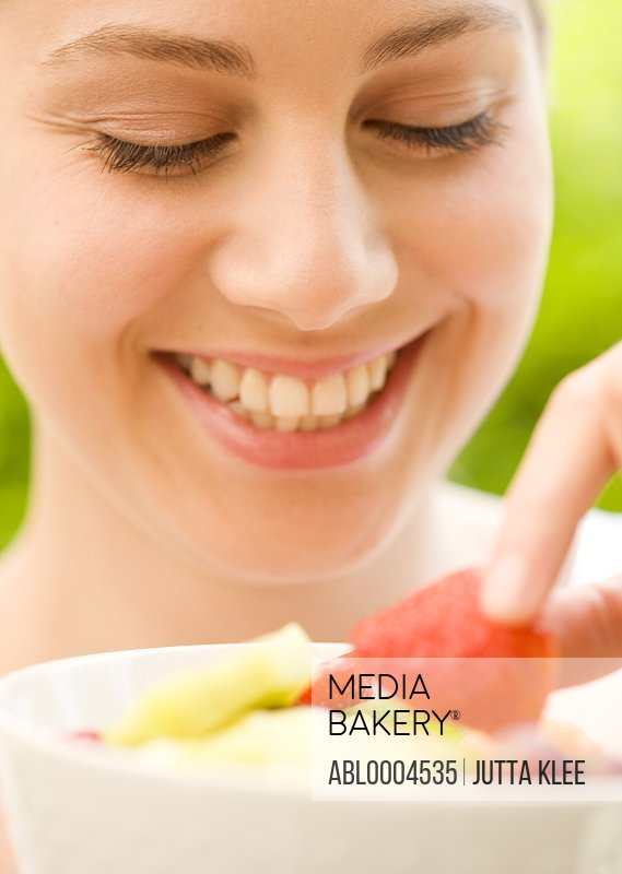 Close up of a young woman holding a strawberry
