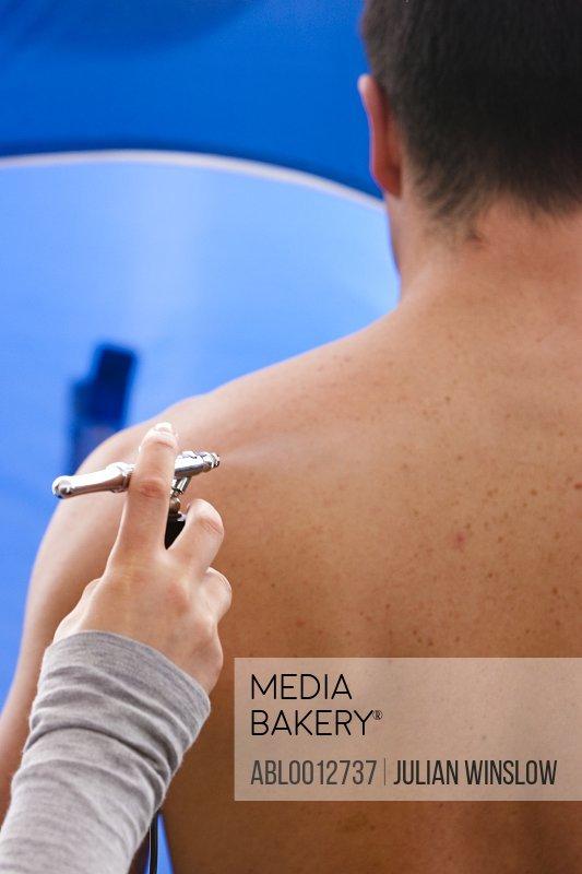 Back view of a man getting a fake tan with an airbrush gun