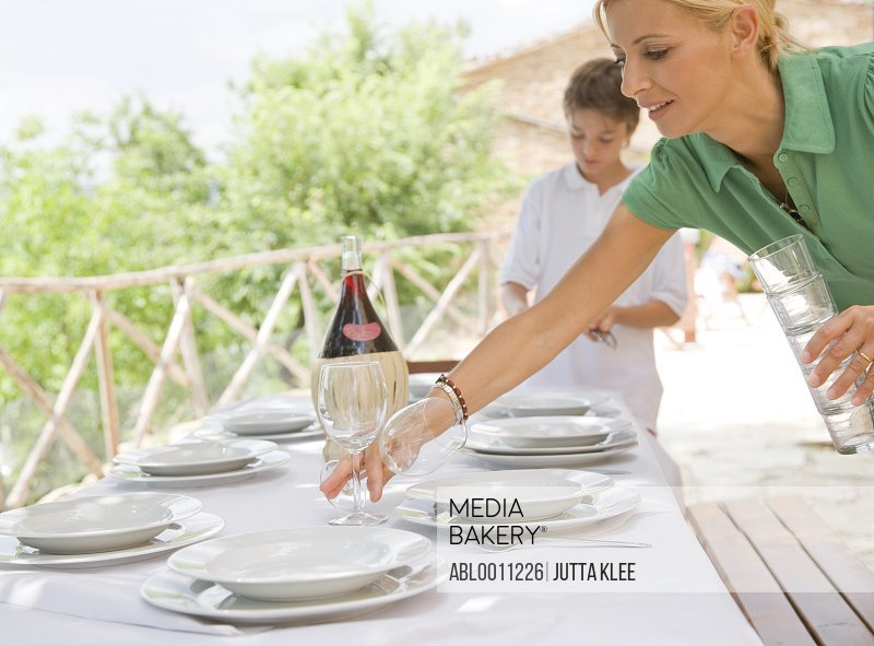 Mother and son setting table