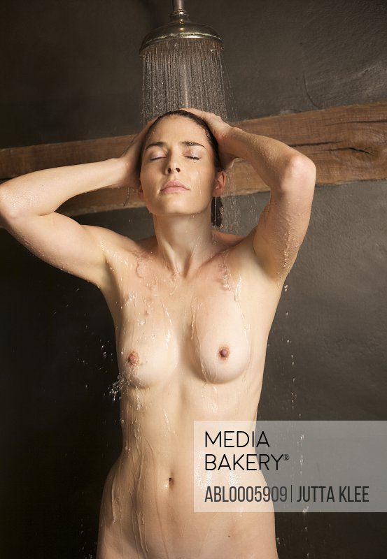 Nude woman rinsing hair under deluge shower