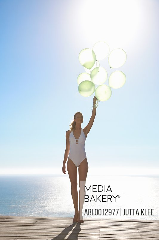 Woman standing on a sun deck holding a bundle of green balloons