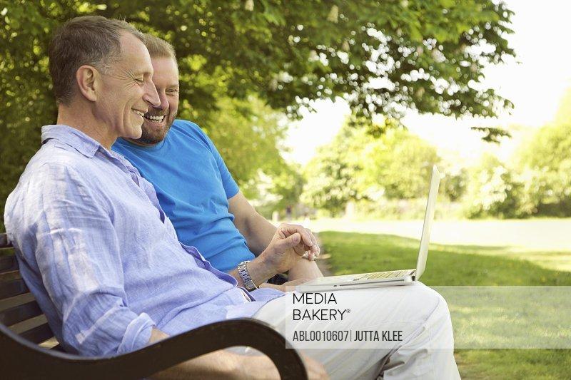 Two Men Sitting on Park Bench Using Laptop Smiling