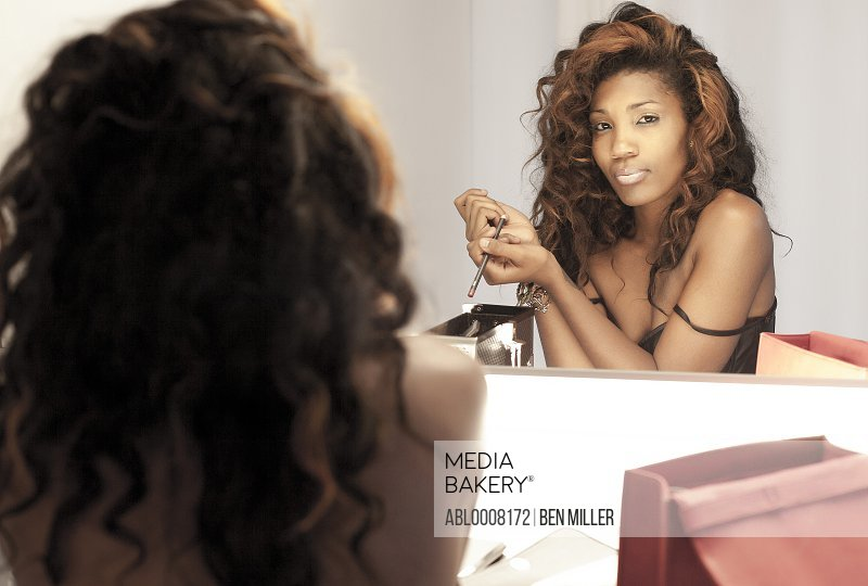 Woman Applying Makeup in front of Dressing Room Mirror