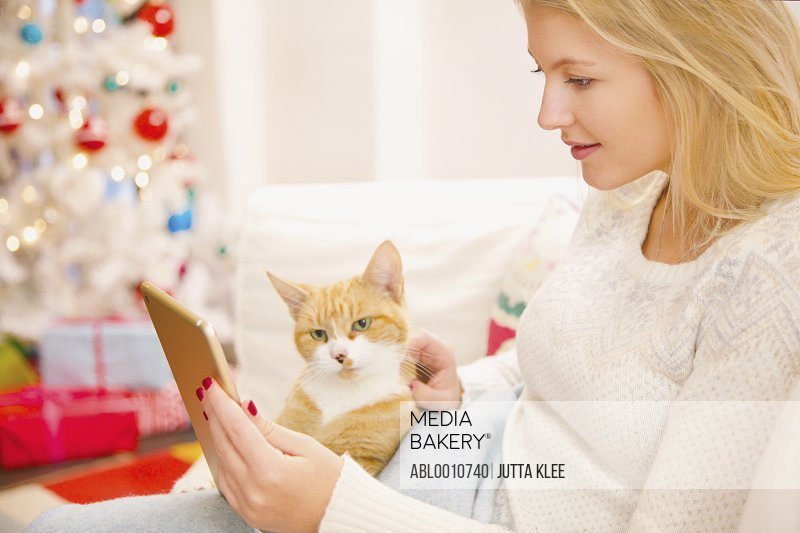 Woman Stroking Cat whilst Using Digital Tablet