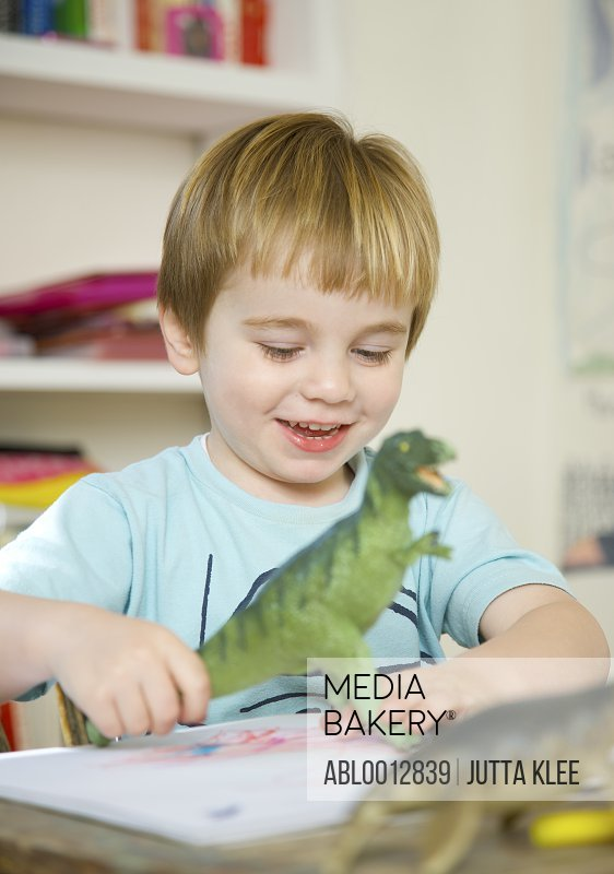 Smiling boy playing with a toy dinosaur
