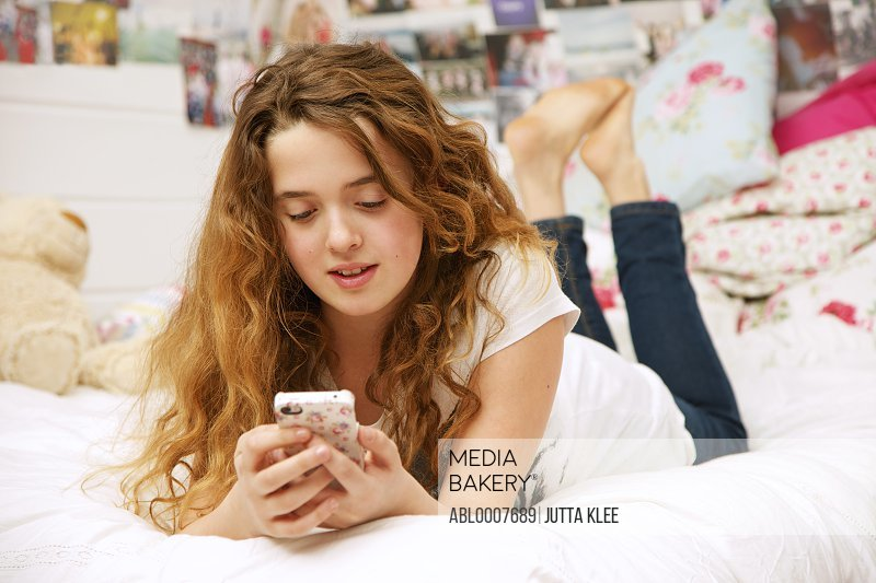 Young Girl Lying on Bed Using Cell Phone