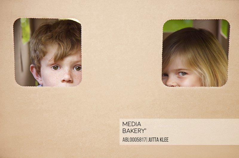 Close up of a boy and girl peeking from the windows of a cardboard playhouse