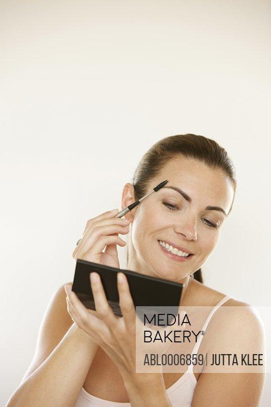 Woman Holding Handheld Mirror Using Eyebrow Brush