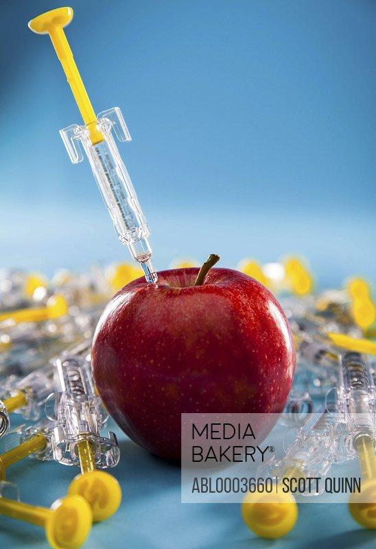 Syringe Injecting Red Apple