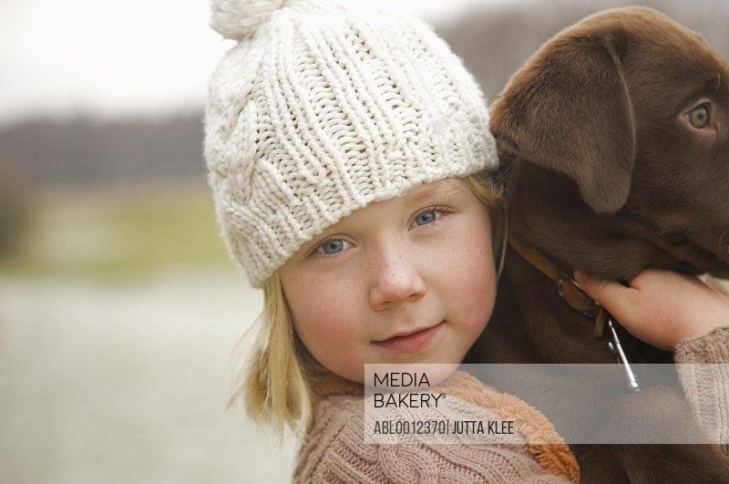 Girl holding a chocolate labrador puppy