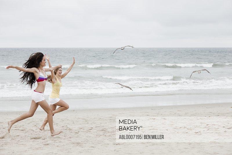 Teenage Girls Chasing Birds on Beach