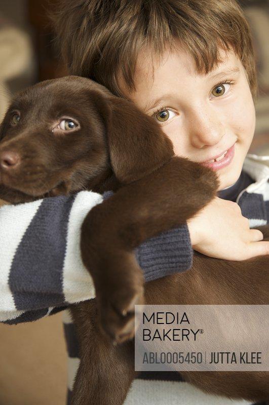 Smiling boy hugging a chocolate labrador puppy