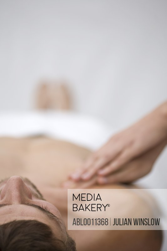 Close up of massage therapist hands massaging man shoulder