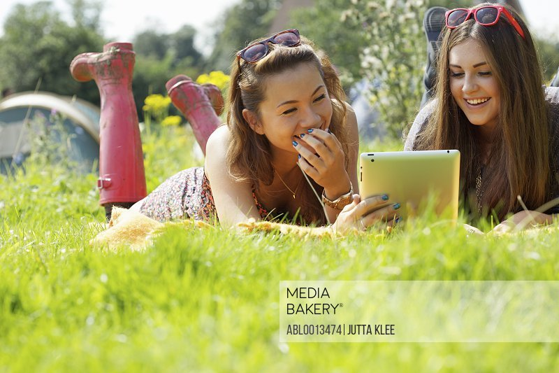 Teenage Girls Lying on Grass Using Tablet