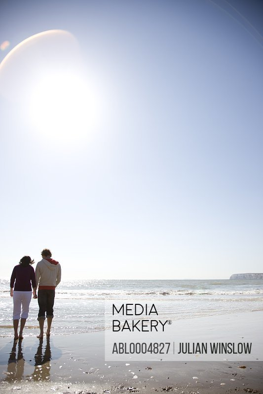 Back of young couple walking on a beach hand in hand