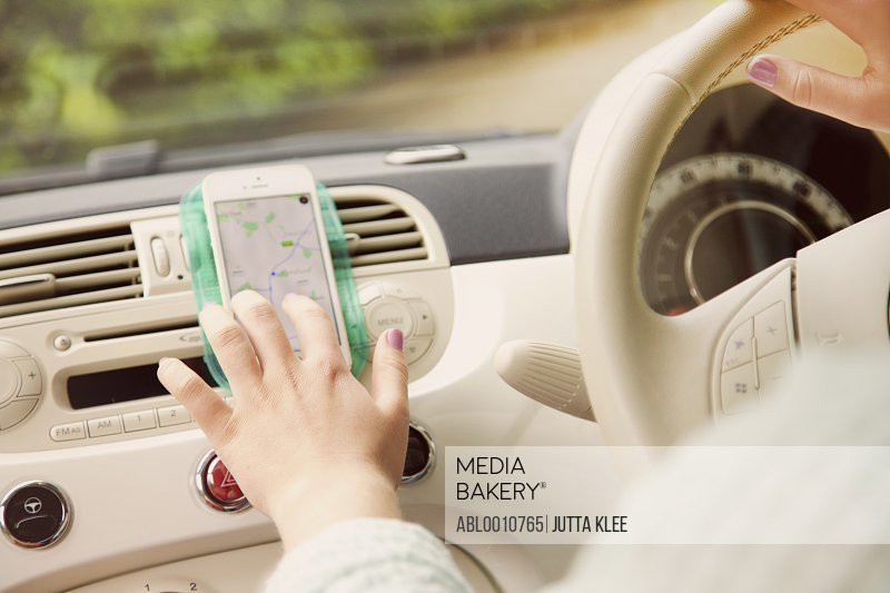 Woman Using Navigation Tool on Smartphone Inside Car, Close-up view