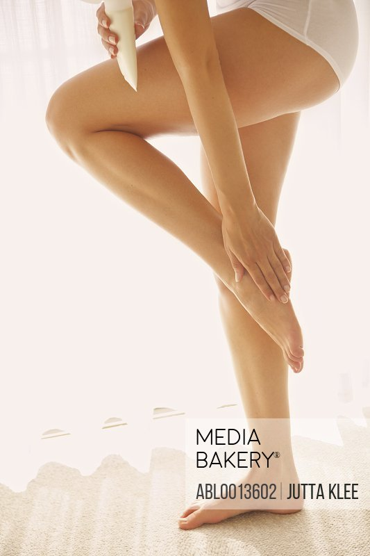 Woman Applying Body Lotion on Foot, Low Section