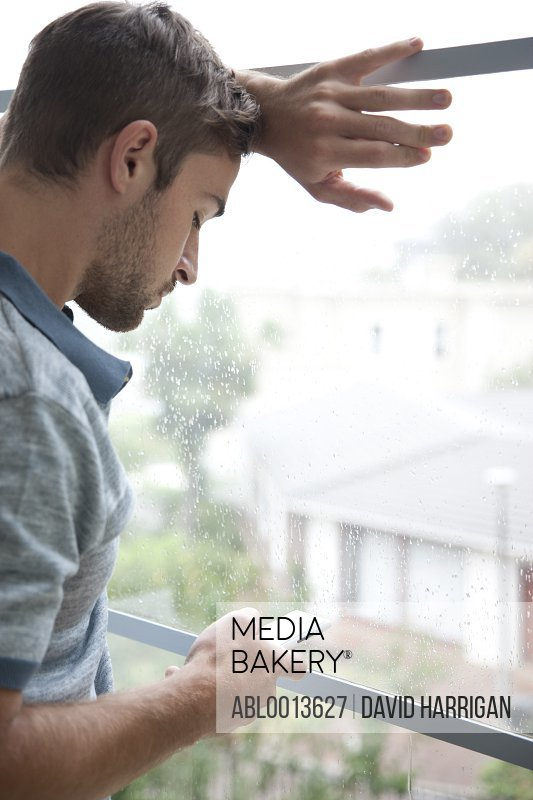 Man Leaning on Window Using Smartphone